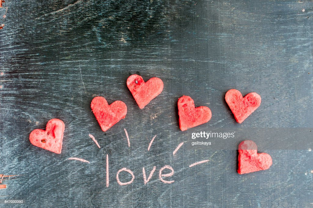 water melon cut into heart shape inscription love with chalk flat