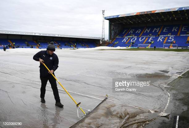 Water on the pitch is removed by members of staff during the FA Cup Fourth Round match between Tranmere Rovers and Manchester United at Prenton Park...