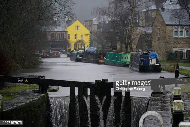 Water over flows the canal lock during heaving rain on January 20, 2021 in Todmorden, United Kingdom. Storm Christoph is the first named storm of...