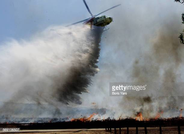 –– Water Over the Dam A water–dropping helicopter aids firefighters battling a five–acre brush fire Tuesday afternoon in the Sepulveda Dam Recreation...