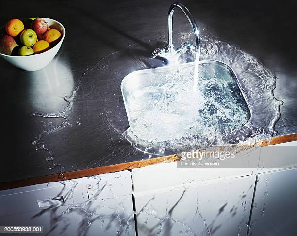water overflowing in kitchen sink, elevated view - lavandino foto e immagini stock