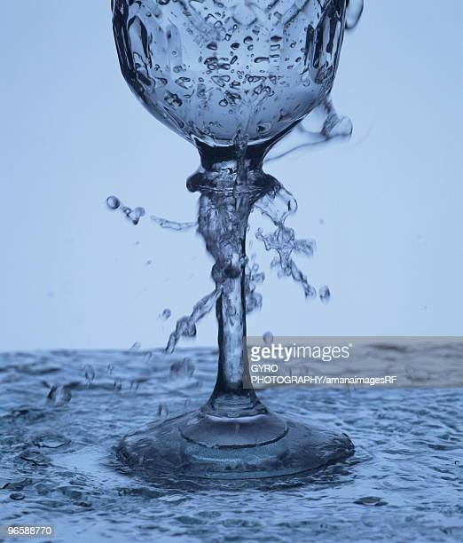 Water overflowing out of a wineglass