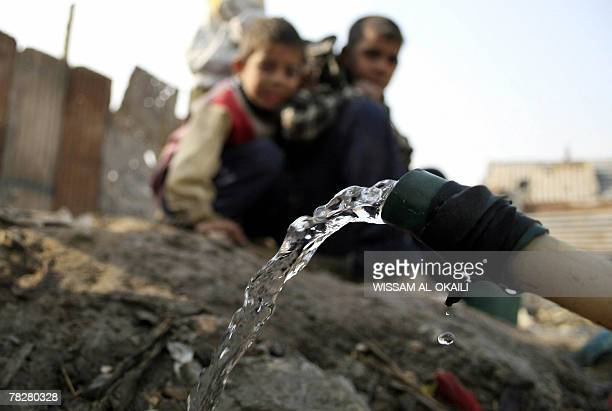 A water pipe that crosses an uncovered sewage canal at the area of Fdailiyah southeast of Baghdad 06 December 2007 trickles water as children look on...