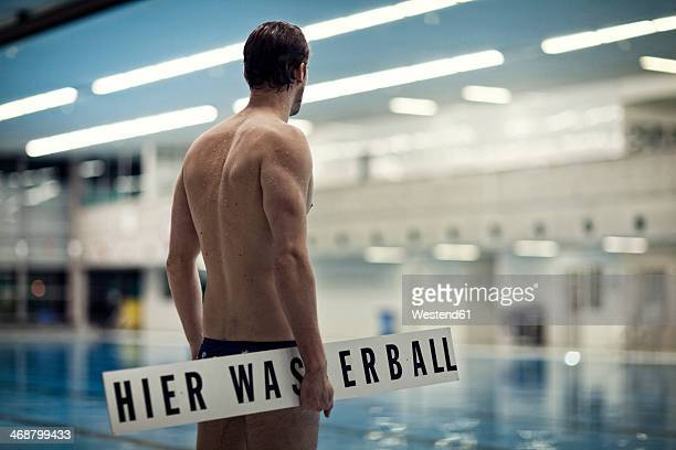 Water polo player carrying sign