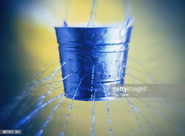 water poring through holes in bucket, close-up - bucket stock pictures, royalty-free photos & images