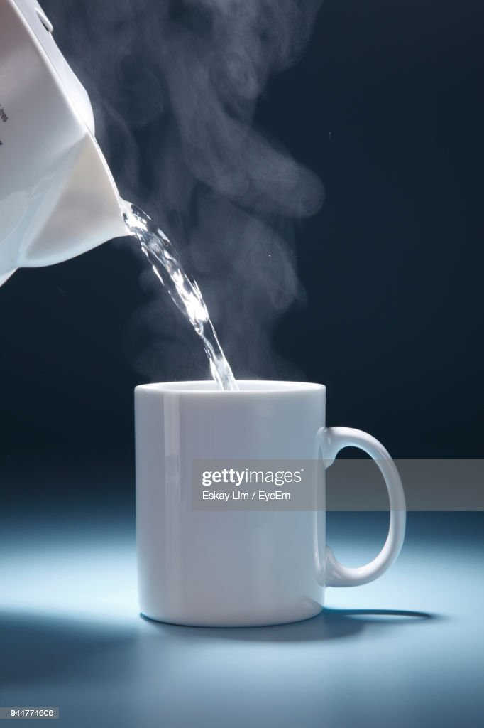 Water Pouring From Pot In Cup Against Black Background : Stock Photo
