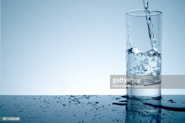 water pouring in glass on table against white background - glass of water stock pictures, royalty-free photos & images