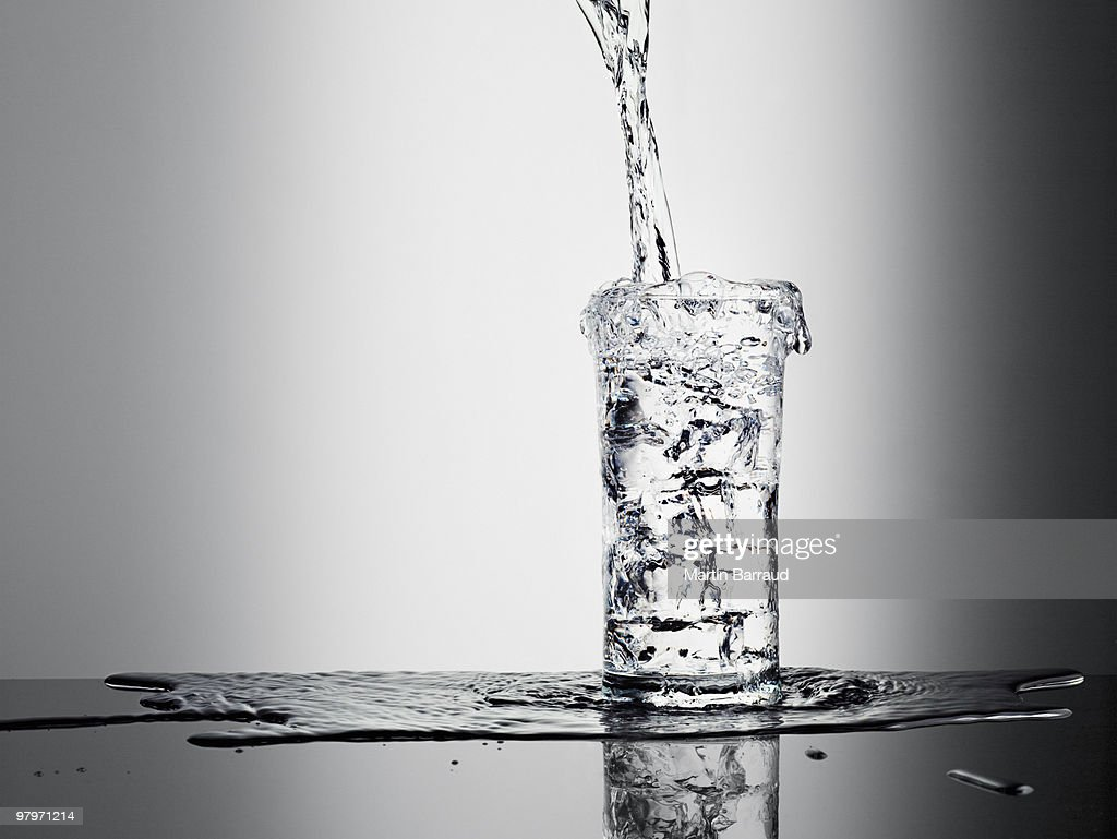 Water pouring into glass and overflowing : Stock Photo