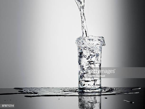 water pouring into glass and overflowing - full stock pictures, royalty-free photos & images