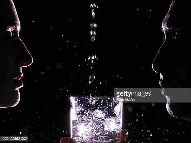 Water pouring into glass between man and young woman, profile