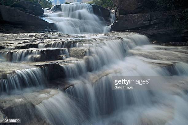 water pouring over the lip of a waterfall, cascades, royal natal, drakensberg ukhahlamba national park, south africa - agua descendente fotografías e imágenes de stock