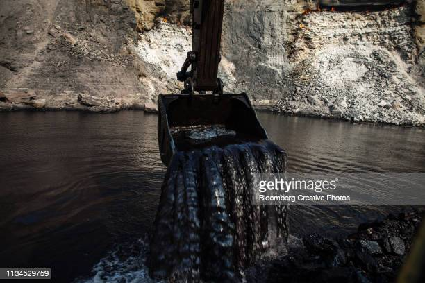 water pours from an excavator bucket as coal is mined from below the water's surface - coal mine stock pictures, royalty-free photos & images