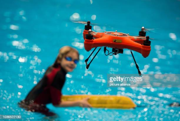 A water proof Splash drone hovering midair after dropping a rescue package for a child in a pool during a press tour at the watersports trade fair...