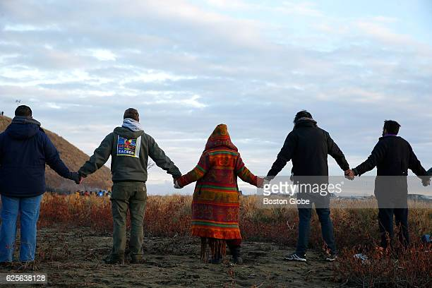 Water protectors join hands in prayer at the end of the day's protest as police line the hill at Standing Rock on Nov. 24 during an ongoing dispute...