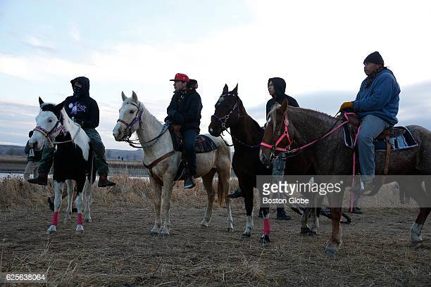 Water protectors on horseback protest as police line the hill at Standing Rock on Nov 24 during an ongoing dispute over the building of the Dakota...