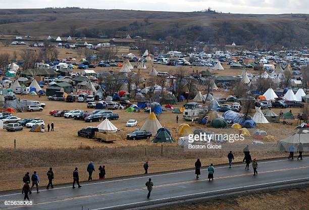 Water protectors peacefully protest along Highway 1806 as they walk past a sprawling encampment at Standing Rock on Nov 24 during an ongoing dispute...
