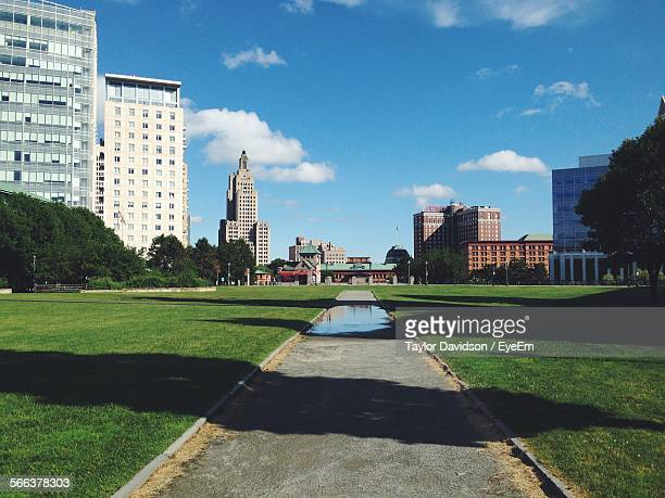 water puddle on garden path in park against blue sky - providence rhode island stock photos and pictures