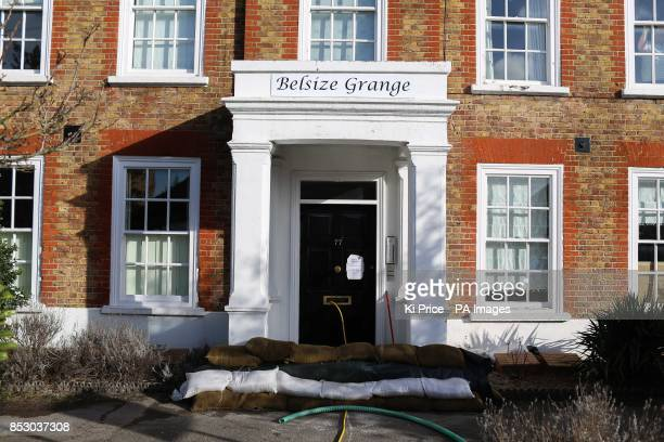 A water pump runs through the letterbox of a house in Chertsey Surrey as two people have died and tens of thousands of homes are without power as...