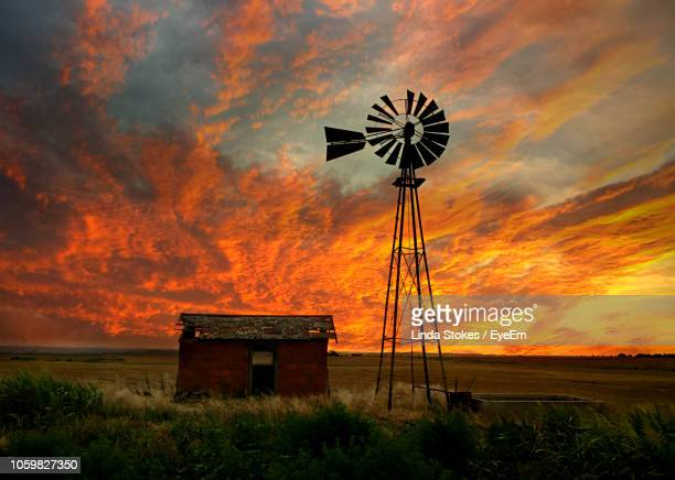 water pump windmill by abandoned barn on field against sky at sunset - old windmill stock photos and pictures
