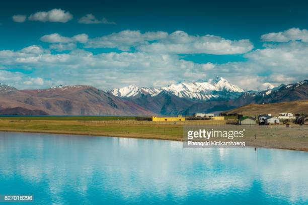 water reflection of town and mountain view from tsomoriri lake, leh ladakh, india - kashmir stock photos and pictures
