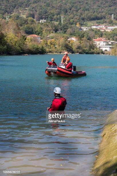 ドライスーツとゴムボート ボート - 川の救助操作の救助労働者を水します。 - 解放する ストックフォトと画像