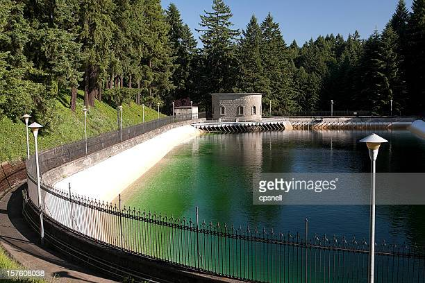 Water reservoir in green forest surrounded by fence and path