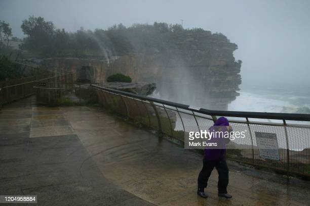 Water rises off the cliffs at Watsons Bay as a sightseer struggles in the wind on February 09 2020 in Sydney Australia The Bureau of Meteorology has...
