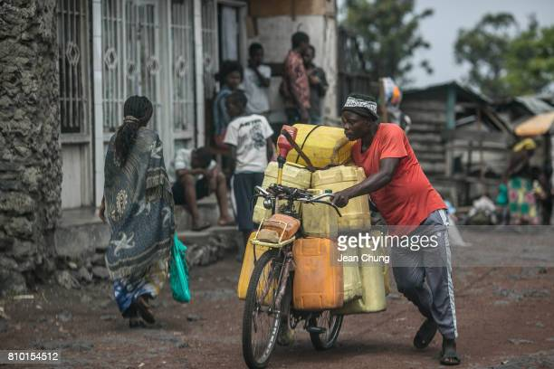 A water seller pushes the bicycle full of water containers in a neighborhood on June 14 2014 in Goma Democratic Republic of Congo Congolese in the...
