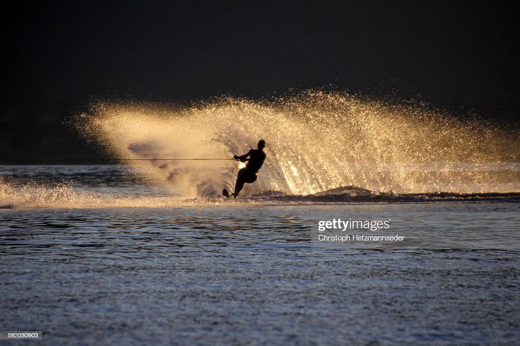 Silhouette of person cuts a turn while water skiing at sunset on Wolfgangsee.