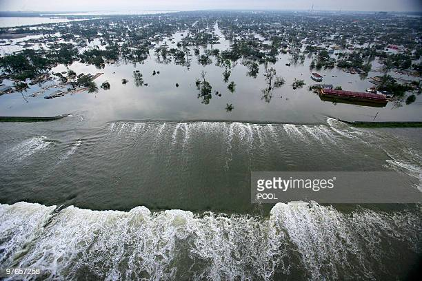 Water spills over a levee along the Inner Harbor Navigational Canal in the aftermath of Hurricane Katrina 30 August 2005 in New Orleans Louisiana It...