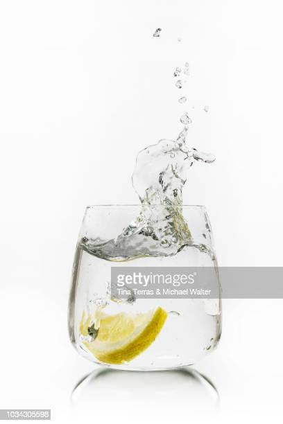 water splash. a glass of water with lemon slice. - tina terras michael walter stock-fotos und bilder
