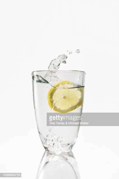 water splash. a glass of water with lemon slice. - kaltes getränk stock-fotos und bilder