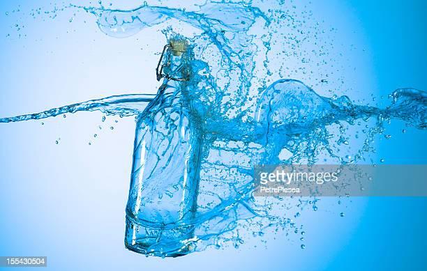 Water Splash auf eine Flasche Wein.  Blau Hintergrund.