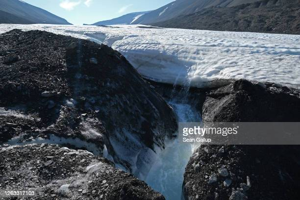 Water splashes down from a winding channel on the surface of the melting Longyearbreen glacier during a summer heat wave on Svalbard archipelago on...