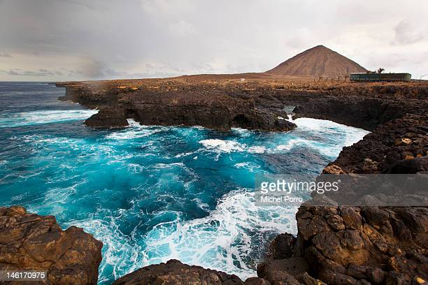 Water splashes near the cliffs by Buracona also called Blue Eye one of the main attractions of the area on May 15 2012 in Sal Rei Cape Verde...