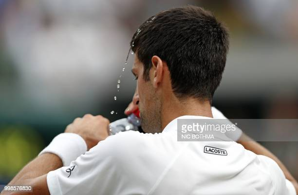 Water splashes off the hair of Serbia's Novak Djokovic during a break playing Spain's Rafael Nadal in their men's singles semifinal match on the...