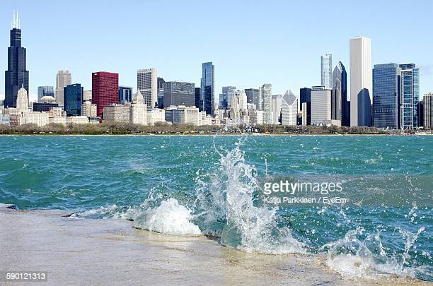 Water Splashing At Lake Michigan By Urban Skyline Against Clear Sky