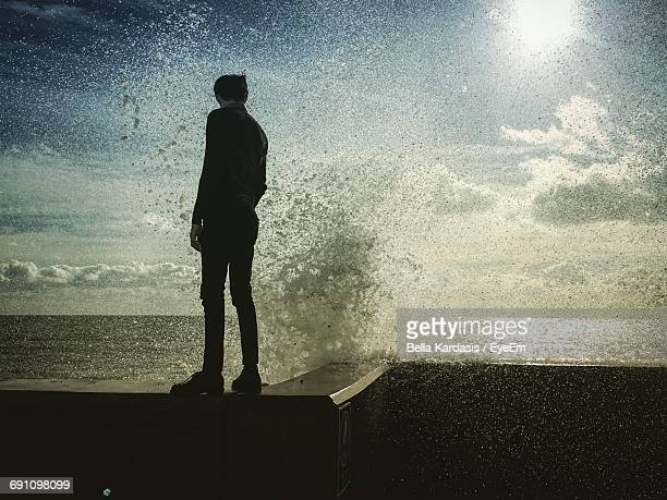 Water Splashing By Man Standing On Retaining Wall Against Sky During Sunny Day