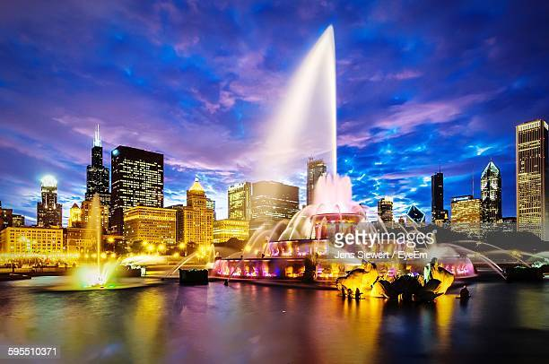 Water Splashing From Buckingham Fountain In Illuminated City Against Sky