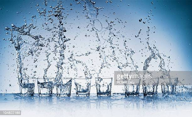 water splashing from glasses - glas materiaal stockfoto's en -beelden