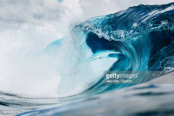 water splashing in sea against sky - breaking wave stock pictures, royalty-free photos & images