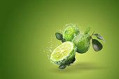 water splashing bergamot fruit green background