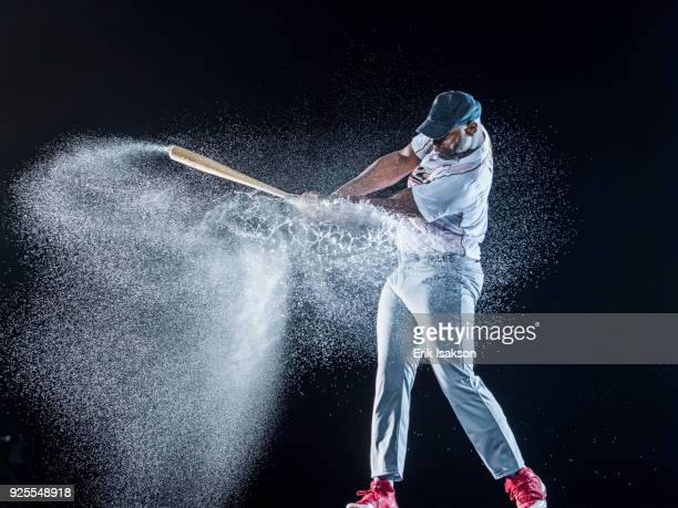 water splashing on black baseball player swinging bat - baseball bat stock pictures, royalty-free photos & images