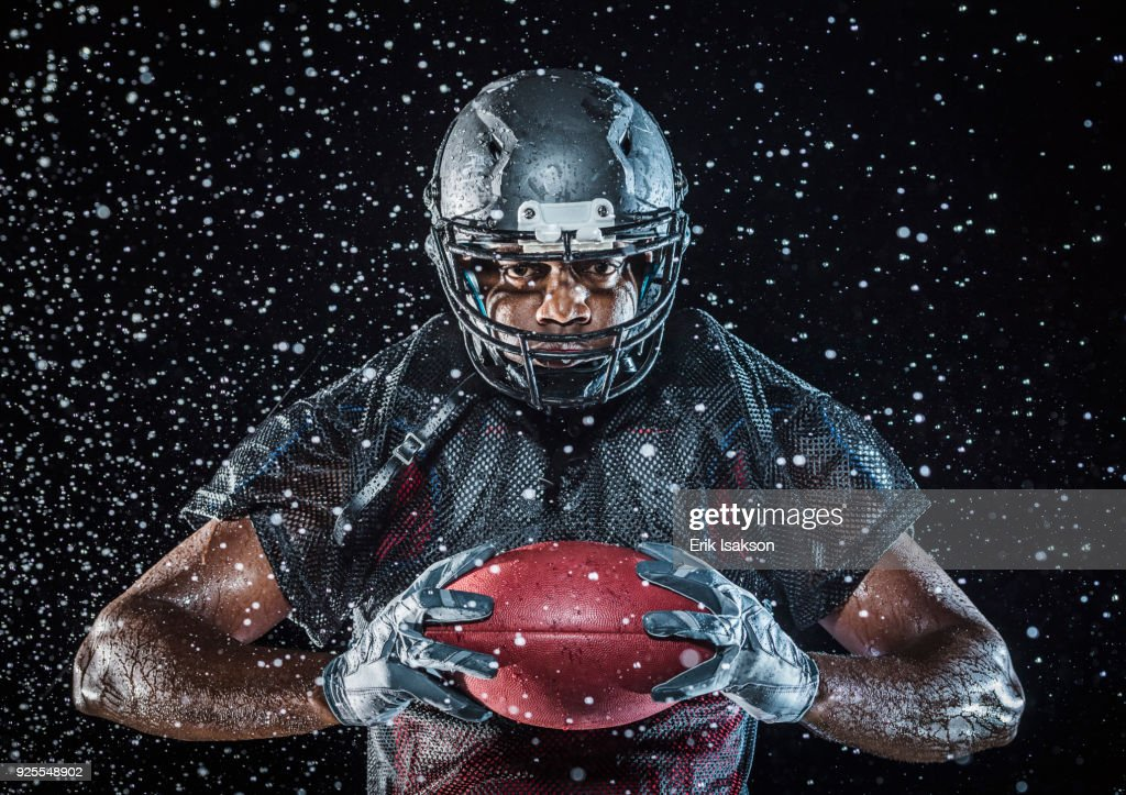 Water splashing on Black football player holding football : Stock Photo