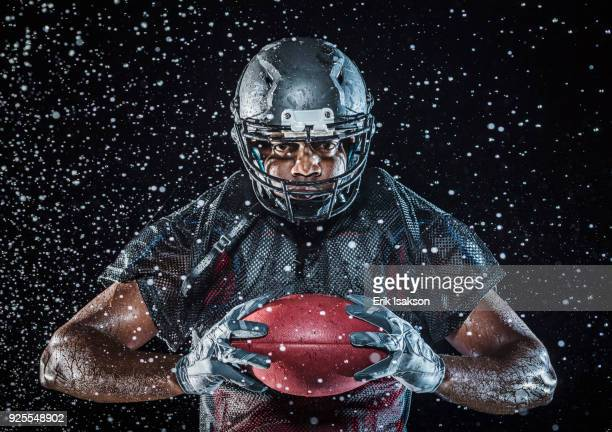 water splashing on black football player holding football - football player stock pictures, royalty-free photos & images