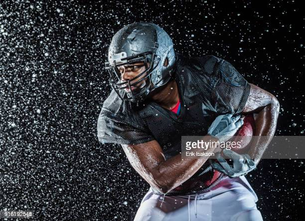 water splashing on black football player - american football player stock pictures, royalty-free photos & images