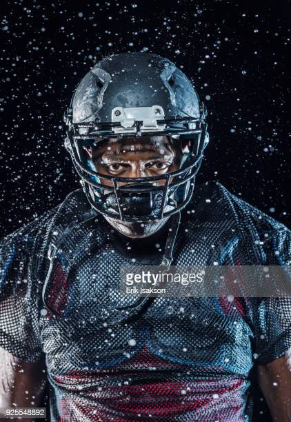 Water splashing on Black football player wearing helmet