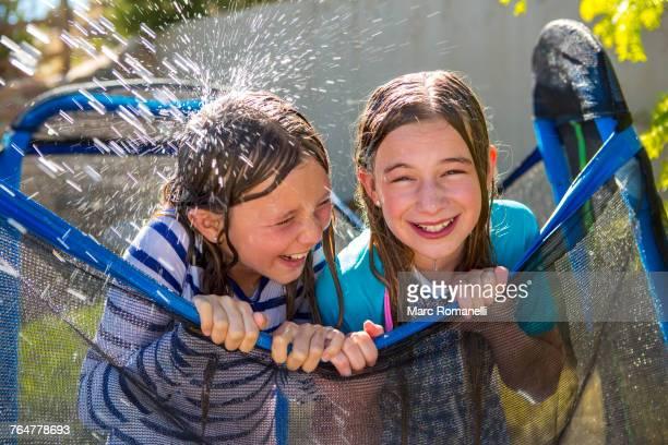 Water splashing on Caucasian girls leaning on netting