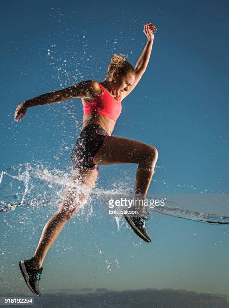 water splashing on caucasian woman running in sky - striding stock pictures, royalty-free photos & images