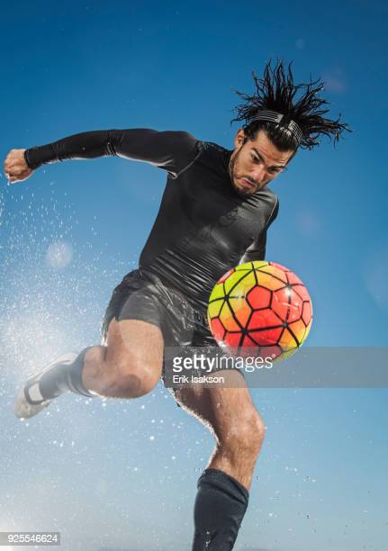 water splashing on hispanic man kicking soccer ball - drive ball sports stock pictures, royalty-free photos & images